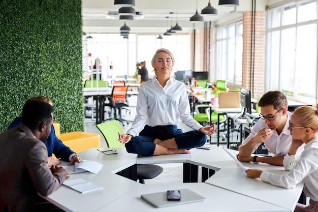 Jovem empresária caucasiana de olhos fechados meditando na mesa do escritório na mesa do trabalho
