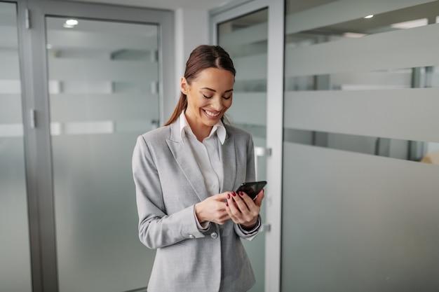 Jovem empresária caucasiana positiva em terno de pé dentro da empresa corporativa e usando telefone inteligente para ler um e-mail.