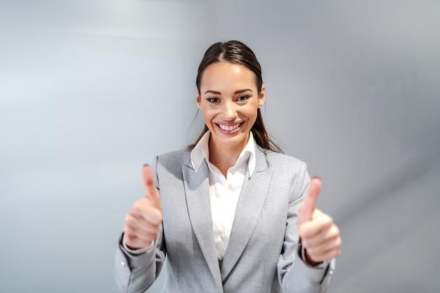Jovem empresária caucasiana sorridente com roupa formal, de pé dentro da empresa corporativa e mostrando os polegares.