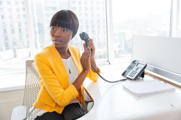 Jovem empresária cobrindo o microfone do telefone e desviando o olhar no escritório