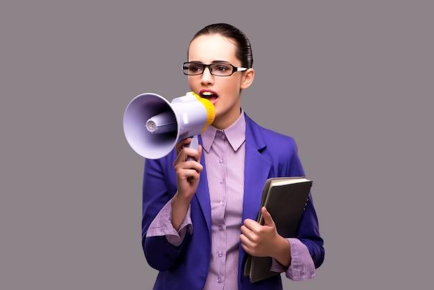 Jovem empresária com alto-falante em fundo cinza