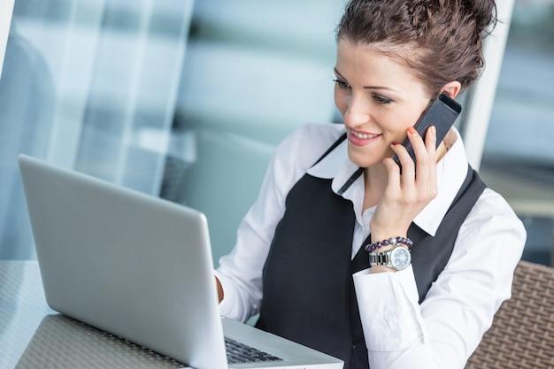 Jovem empresária com computador e celular