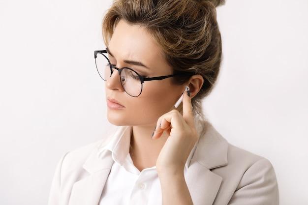Jovem empresária com fones de ouvido sem fio nas orelhas