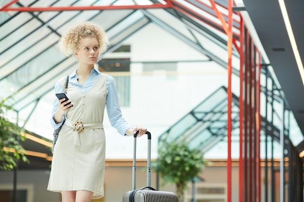 Jovem empresária com mala viajando, ela está no aeroporto