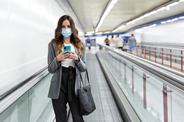 Jovem empresária com máscara facial andando com o smartphone na mão