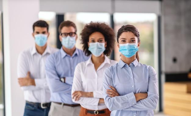 Jovem empresária com máscara facial em pé na empresa corporativa com os braços cruzados. atrás dela estão seus colegas de braços cruzados e máscaras faciais também. embora seja corona, o negócio não pode parar.