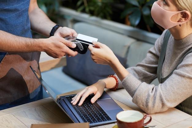 Jovem empresária com máscara protetora, pagando com cartão de crédito, enquanto está sentada à mesa em frente ao laptop no café