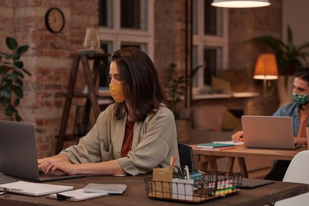 Jovem empresária com máscara protetora sentada à mesa e digitando no laptop no escritório à noite