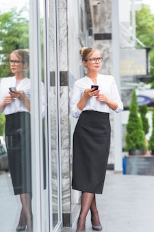 Jovem empresária com smartphone a desviar o olhar