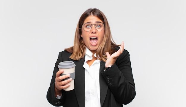 Jovem empresária com um café parecendo desesperada e frustrada, estressada, infeliz e irritada, gritando e gritando
