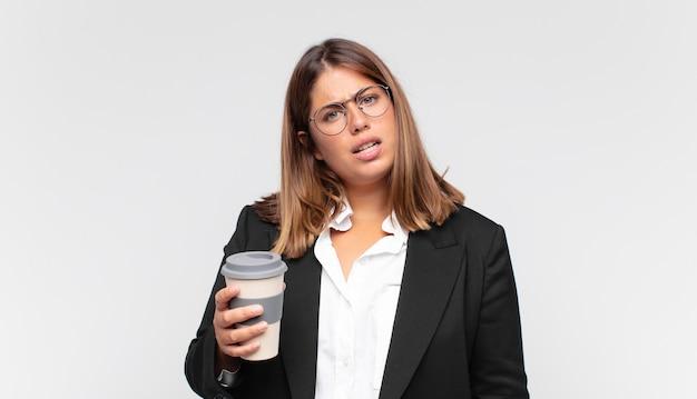 Jovem empresária com um café se sentindo perplexa e confusa, com uma expressão estúpida e atordoada olhando para algo inesperado