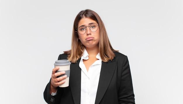 Jovem empresária com um café se sentindo triste e chorona com um olhar infeliz, chorando com uma atitude negativa e frustrada