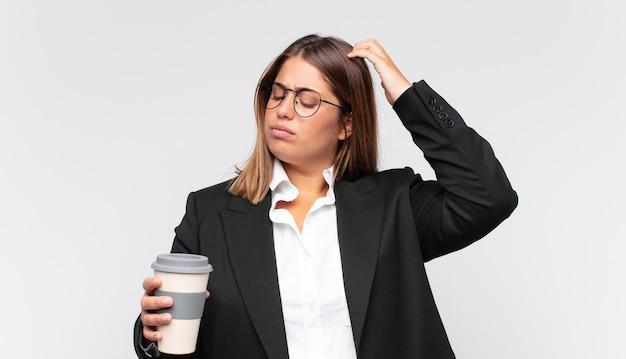 Jovem empresária com um café sentindo-se perplexa e confusa, coçando a cabeça e olhando para o lado