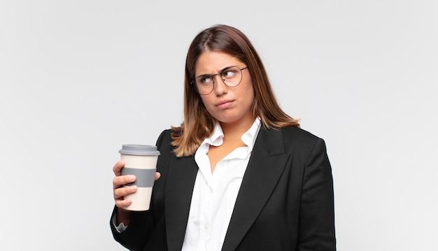 Jovem empresária com um café sentindo-se triste, chateada ou com raiva e olhando para o lado com uma atitude negativa, franzindo a testa em desacordo