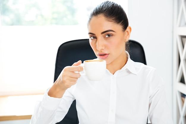 Jovem empresária concentrada tomando café no escritório e olhando para a frente