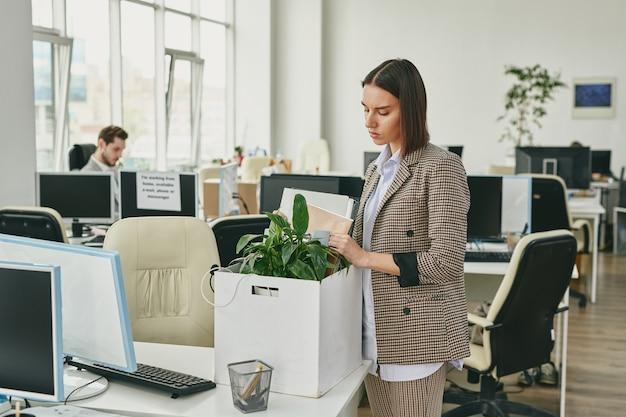 Jovem empresária contemporânea colocando plantas verdes e documentos na caixa enquanto sai do escritório e trabalha em casa