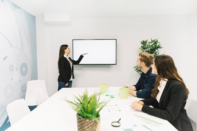 Jovem empresária dando apresentação para seus colegas em reunião de negócios