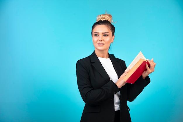 Jovem empresária de blazer preto segurando um caderno de tarefas e lendo-o.