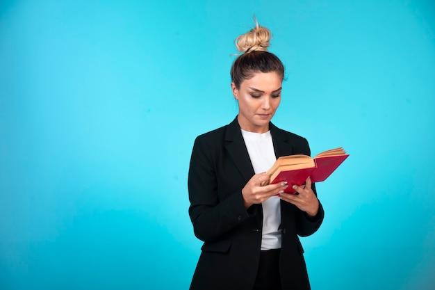 Jovem empresária de blazer preto segurando um caderno de tarefas e verificando as reuniões.