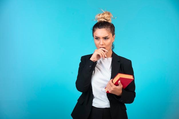 Jovem empresária de blazer preto segurando um livro e pensando