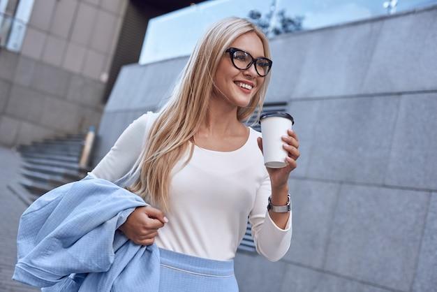 Jovem empresária de óculos sorrindo e andando perto do prédio comercial com café