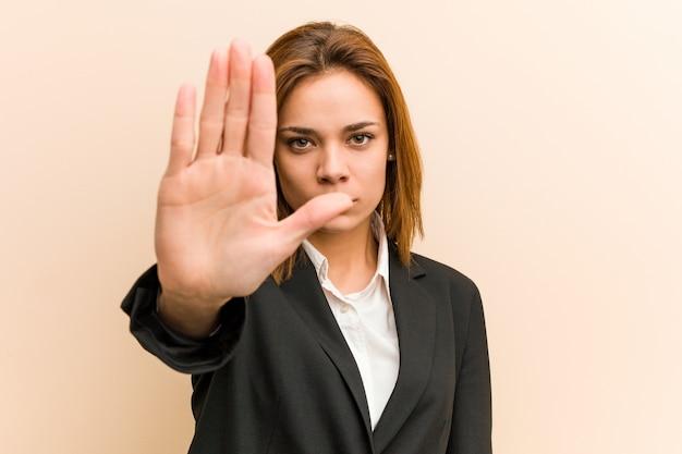 Jovem empresária de pé com a mão estendida, mostrando o sinal de stop