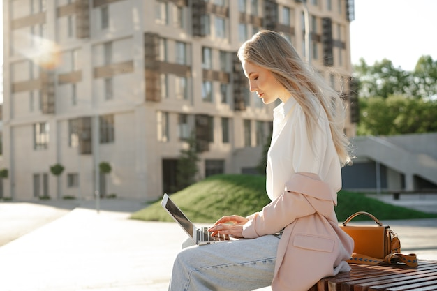 Jovem empresária de sucesso usando laptop para trabalhar ao ar livre