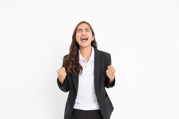 Jovem empresária de terno preto com expressão animada aos gritos