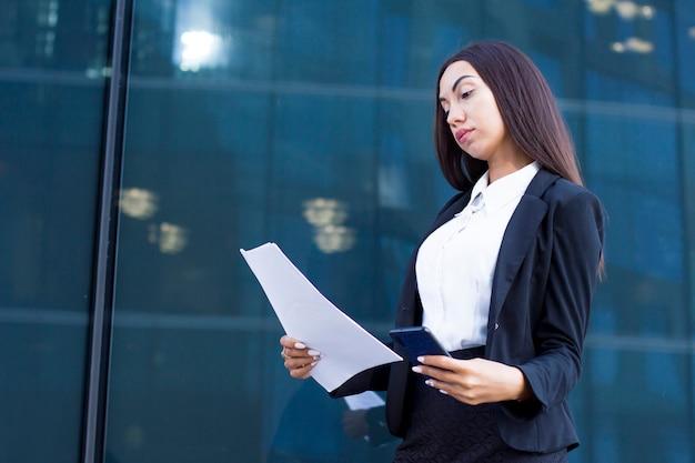 Jovem empresária de terno segurando documentos, smartphone nas mãos. leitura ocupada séria bonita do trabalhador fêmea ao ar livre.