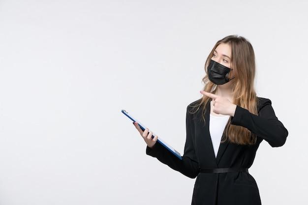 Jovem empresária de terno usando sua máscara médica e segurando documentos apontando algo na parede branca