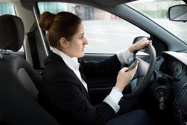Jovem empresária digitando mensagem enquanto dirige um carro