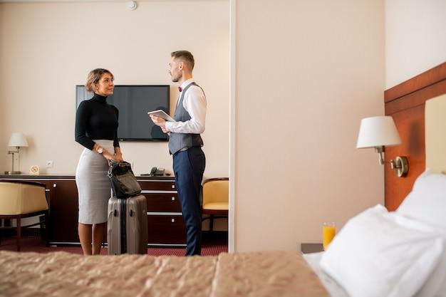 Jovem empresária elegante com mala e bolsa em pé no quarto do hotel na frente do porteiro durante uma conversa