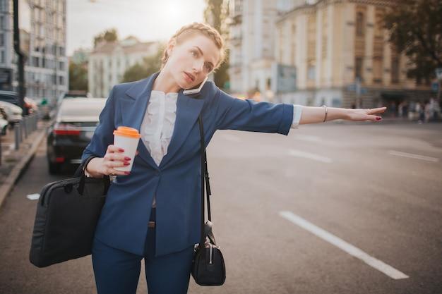 Jovem empresária elegante com uma xícara de café, pegar um táxi
