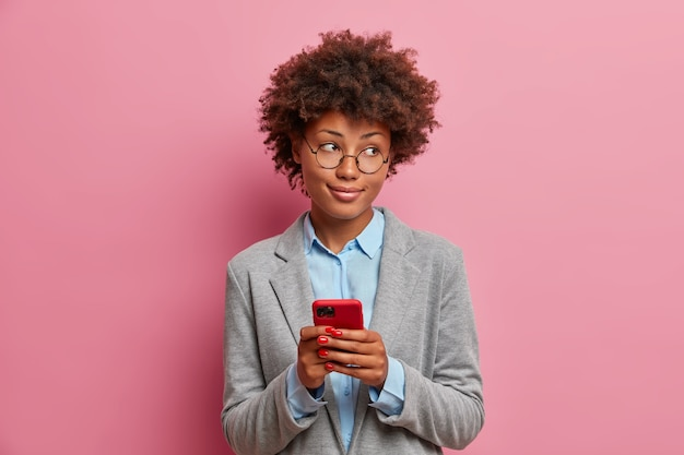 Jovem empresária elegante, vestida com roupas formais elegantes, segura o celular, envia mensagens, bate-papo online, percorre redes sociais, lê artigo na internet