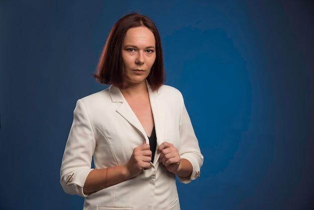 Jovem empresária em blazer branco parece profissional.