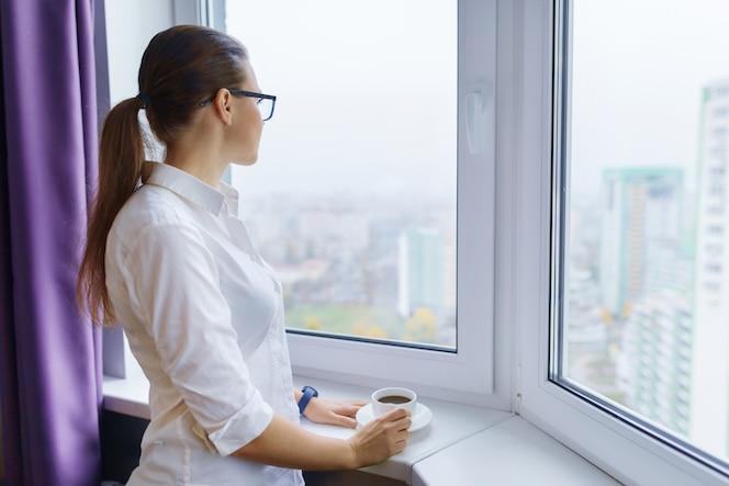 Jovem empresária em copos com uma xícara de café perto da janela