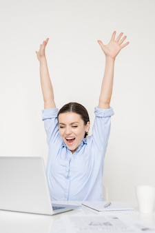 Jovem empresária em êxtase ou freelancer em roupas casuais, levantando os braços de alegria enquanto olha para a tela do laptop