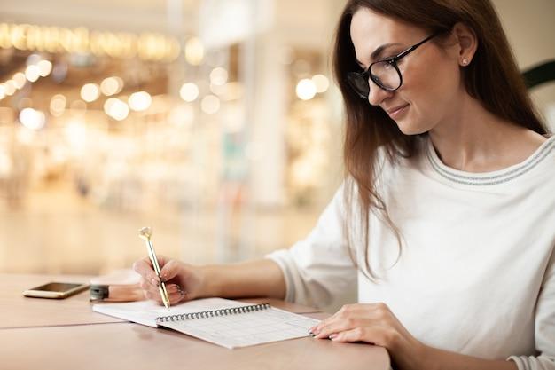 Jovem empresária em óculos, planejando e anotando a programação diária com a ordem do dia