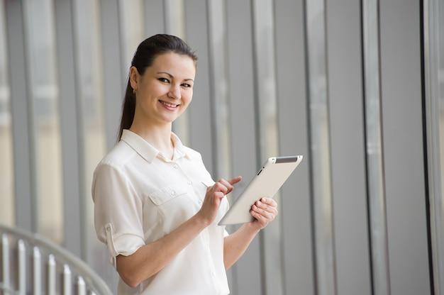 Jovem empresária em pé junto à janela com computador tablet.