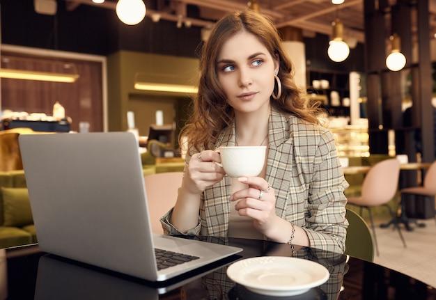Jovem empresária em roupa casual inteligente bebe café e trabalhando no laptop