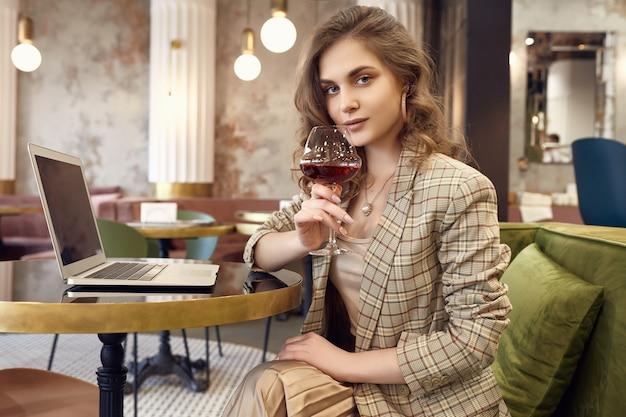 Jovem empresária em roupa casual inteligente bebe vinho e trabalhando no laptop