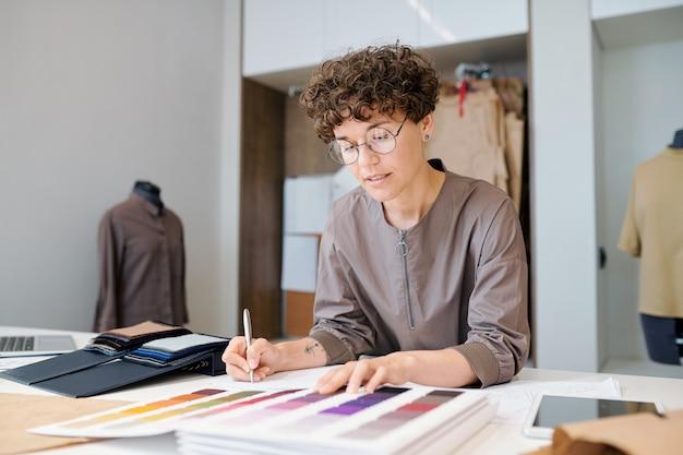 Jovem empresária em roupas casuais e óculos olhando uma coleção de amostras têxteis enquanto escolhe uma