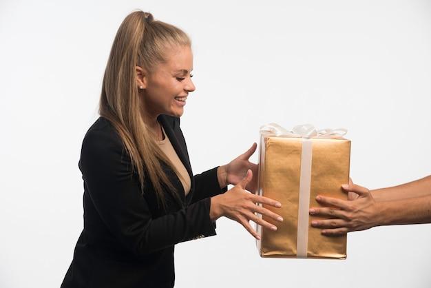 Jovem empresária em terno preto levando uma caixa de presente e sorrindo.