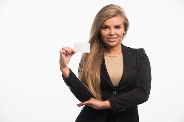 Jovem empresária em terno preto, verificando o cartão do cliente e sorrindo.