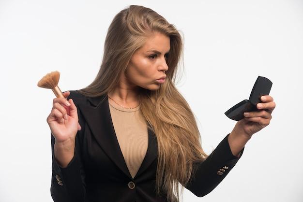 Jovem empresária em um terno preto, aplicando maquiagem e olhando para o espelho.