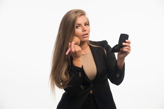 Jovem empresária em um terno preto, aplicando maquiagem na bochecha.