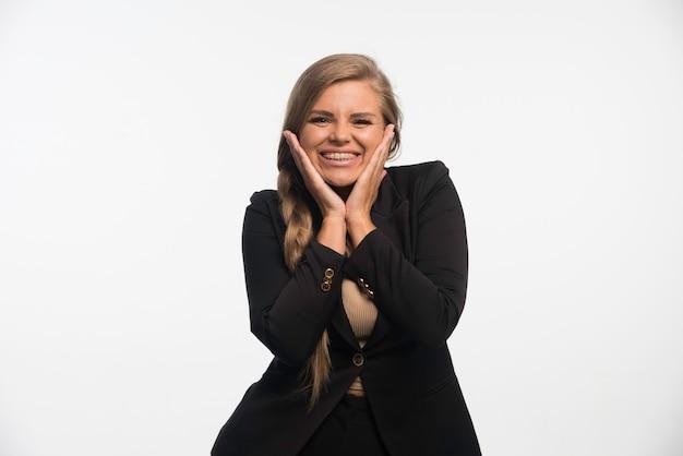Jovem empresária em um terno preto parece feliz e alegre.