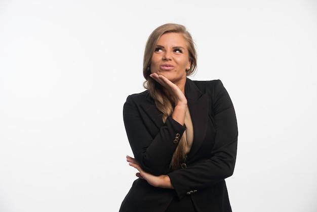 Jovem empresária em um terno preto parece feliz e confiante.