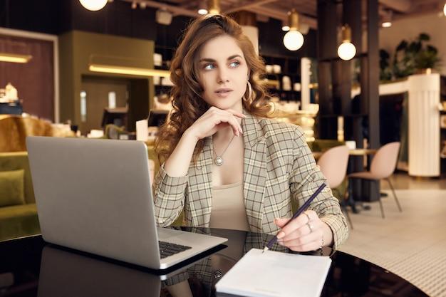 Jovem empresária em vestuário casual inteligente faz anotações em um caderno no interior de uma cafeteria
