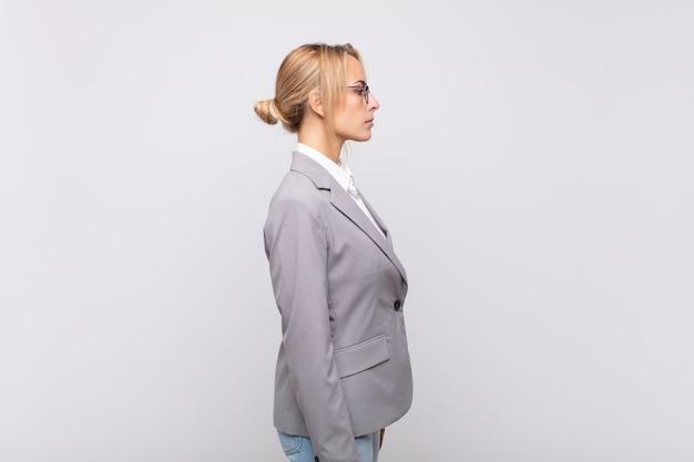 Jovem empresária em vista de perfil olhando para copiar o espaço à frente, pensando, imaginando ou sonhando acordada